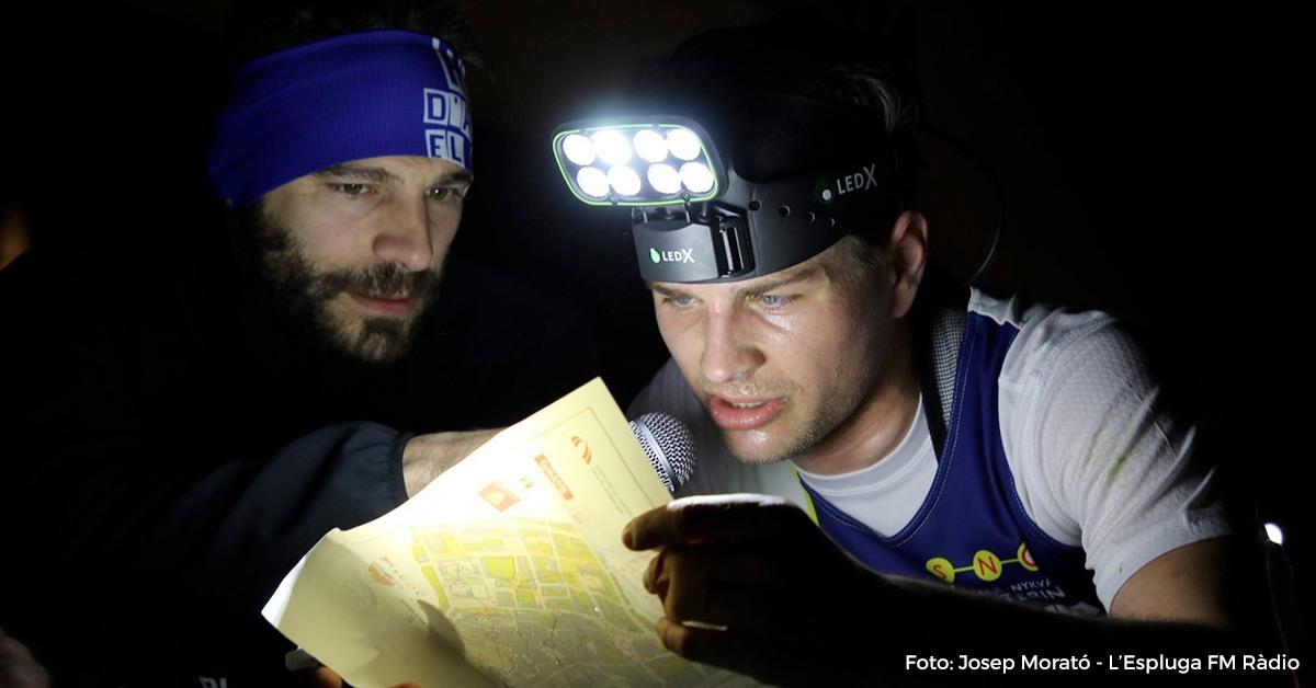 home esportista mirant mapa amb llanterna enmig d'una cursa d'orientació a Montblanc