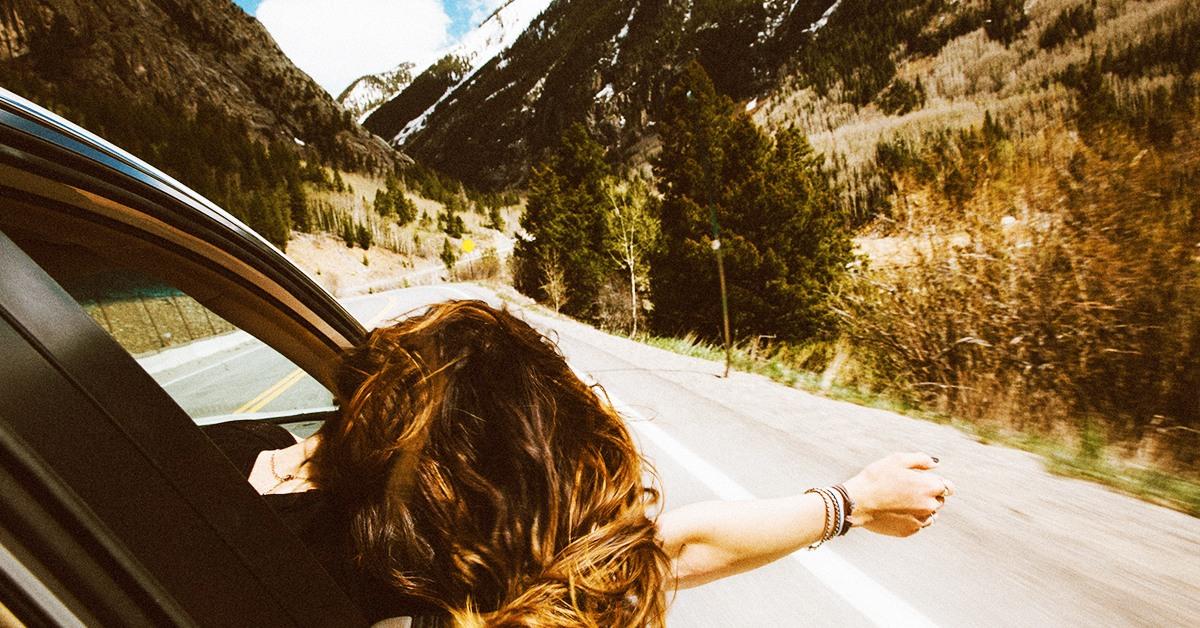 Conducció i visió. Noia traient el braç per la finestra del cotxe